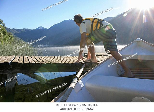 Mature man launches rowboat from dock in mountain lake