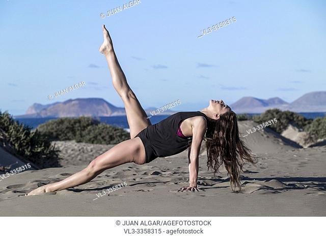 Side view of brunette practicing yoga on sandy beach raising leg up on blue sky background