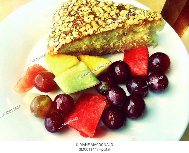 Slice of cake and fresh fruit pieces on plate