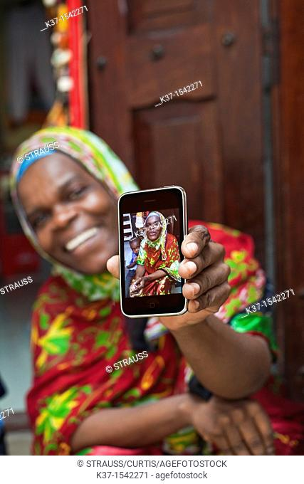 Local woman in East African market and holding smart phone with her photo