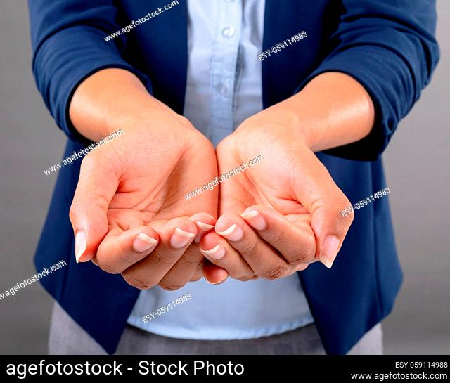 Mid section of businesswoman with cupped hands against grey background