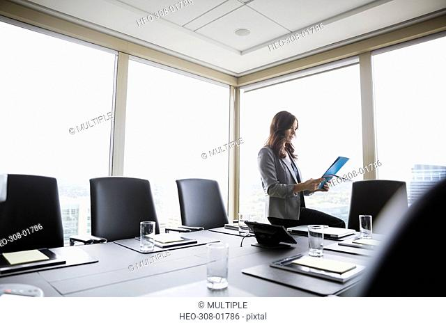 Businesswoman preparing for meeting using digital tablet in conference room