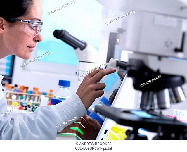 STEM scientist in the laboratory using a touch screen computer to analyse data from an experiment