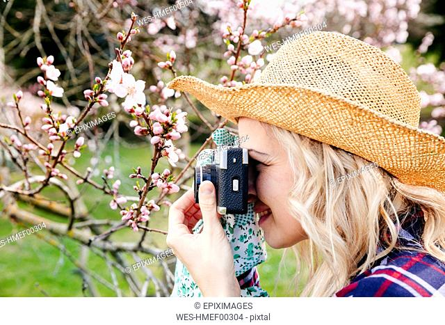 Young woman with a straw hat taking pictures in the garden with an old camera