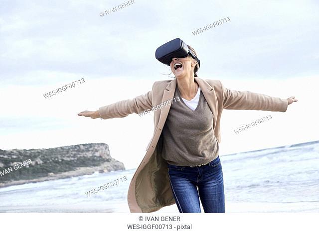 Spain, Menorca, senior woman using VR glasses on the beach in winter