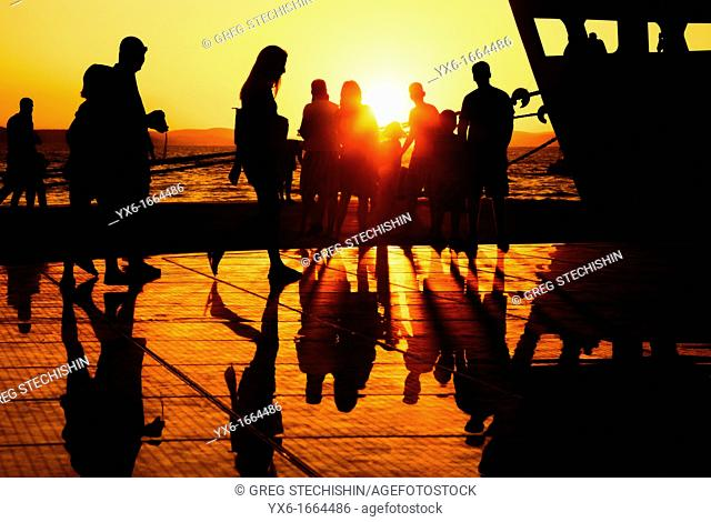 People enjoying the sunset on a warm summer evening at the Sun Salutation on the ground in Zadar, Croatia  Designed by architect Nikola Basic
