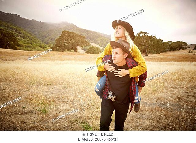 Caucasian man carrying girlfriend in rural landscape