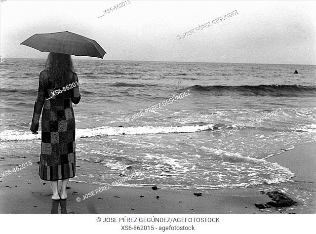 Young woman standing under cloudy sky