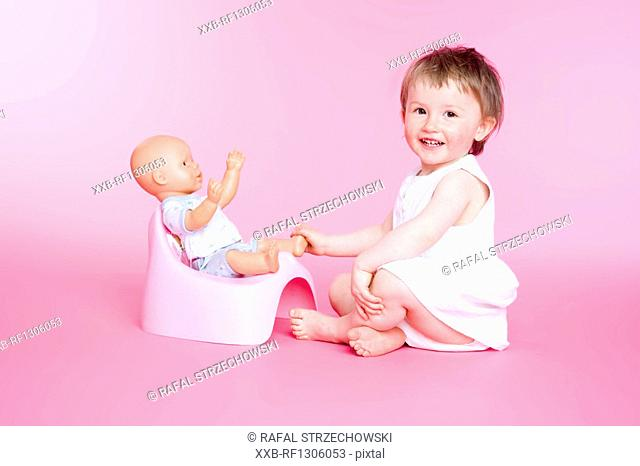 girl with doll on her toilet