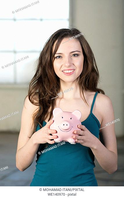 Happy young woman holding a piggy bank