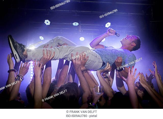 Group of people lifting man in club