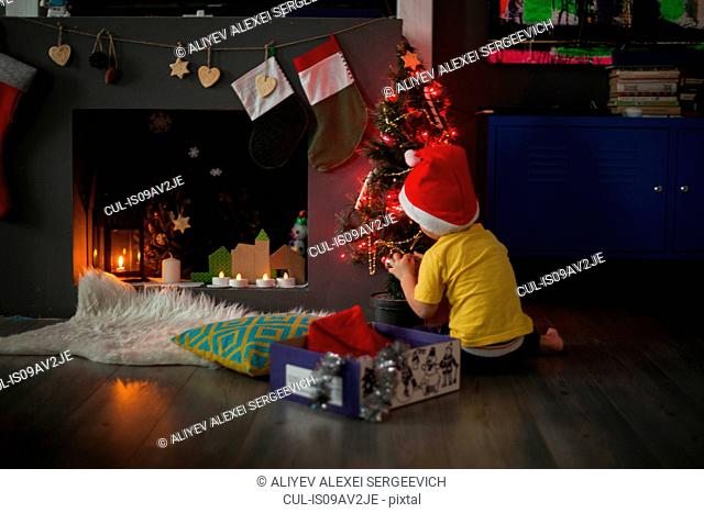 Male toddler preparing christmas tree in front of fireplace