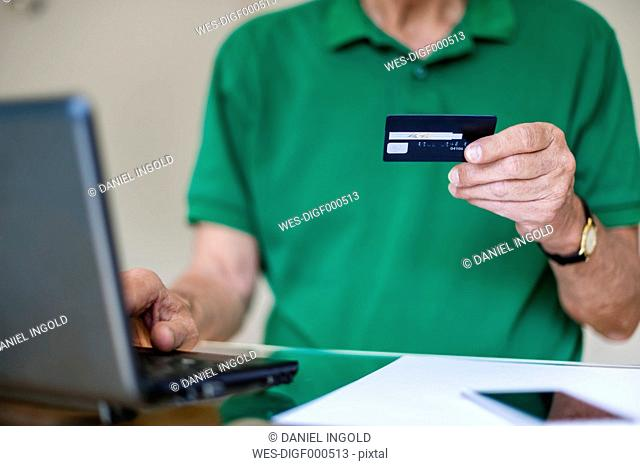 Senior man with laptop and credit card shopping online