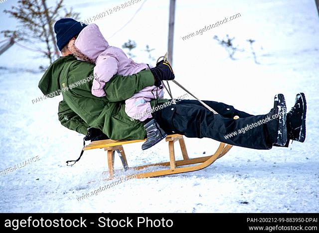 12 February 2020, Saxony, Altenberg: A man with his toddler on his lap toboggans down the ski slope in partly sunny weather