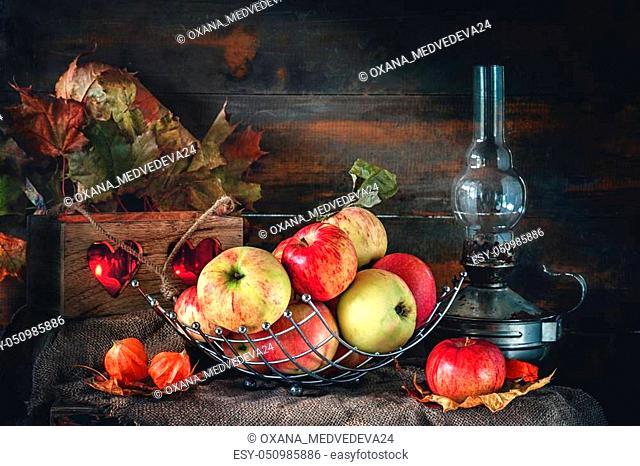 Autumn still life of apples in a basket with a lamp and candles. The horizontal frame