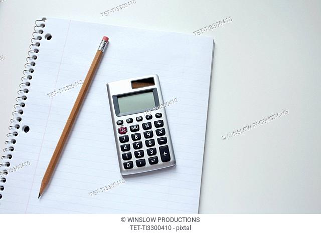 Calculator and pencil on notepad, studio shot