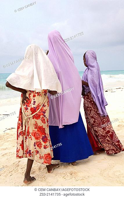 Young muslim girls in colorful dress on Nungwi beach, Zanzibar Island, Tanzania, East Africa