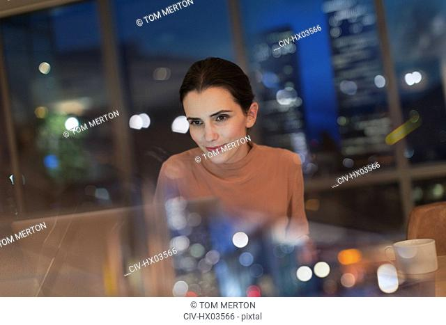 Businesswoman working late at laptop in office at night
