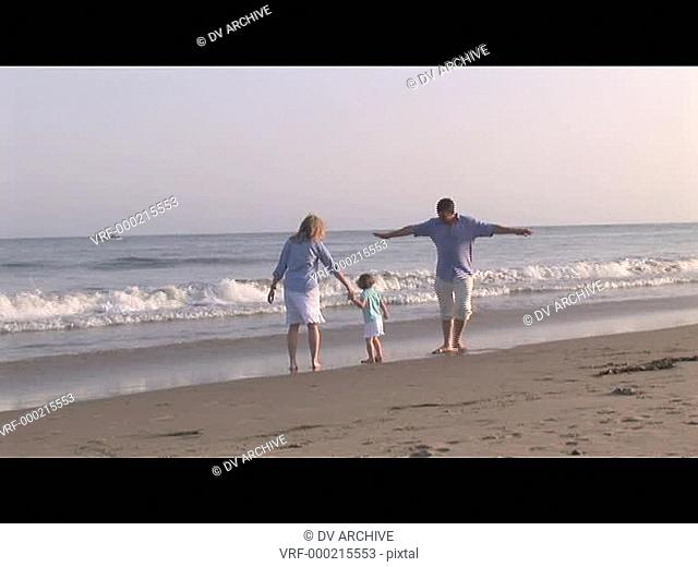 Medium shot of family playing on the beach