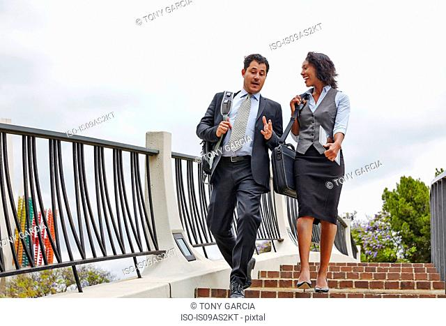 Low angle view of business people descending stairway carrying briefcases and digital tablet
