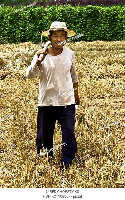 Mature man holding pitchfork in a field, Zhigou, Shandong Province, China