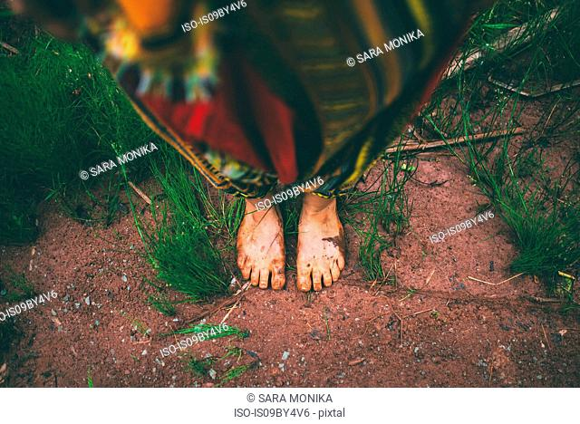 Woman standing barefoot in forest