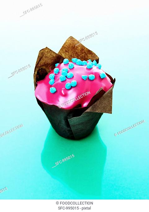 Muffin with pink icing in baking parchment