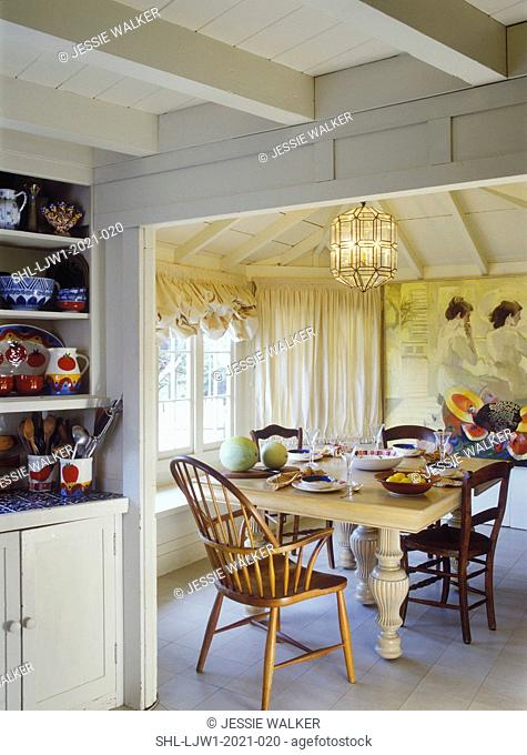 EATING AREAS: Cottage, exposed ceiling, beige and ivory mural painted on wall, partial view of kitchen shelves with colorful pottery balloon shades