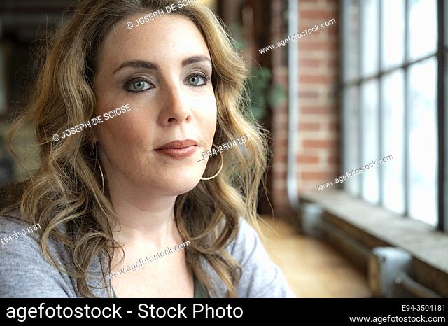 A portrait of a pretty 37 year old woman looking directly at the camera