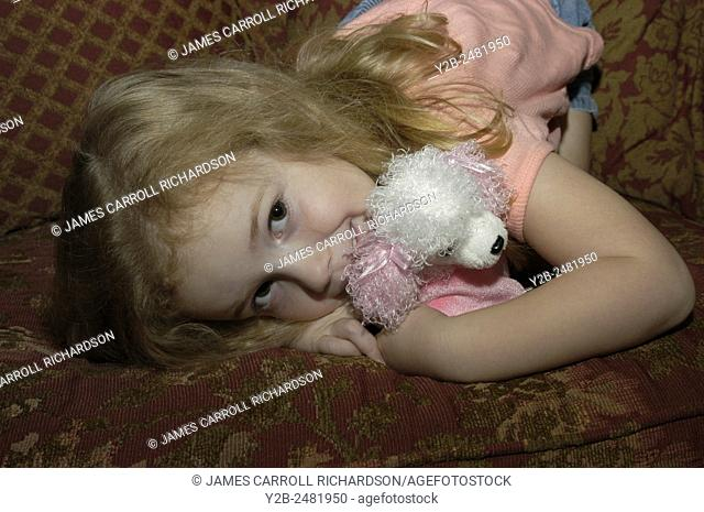 Young girl lying on couch with stuffed animal smiling shyly