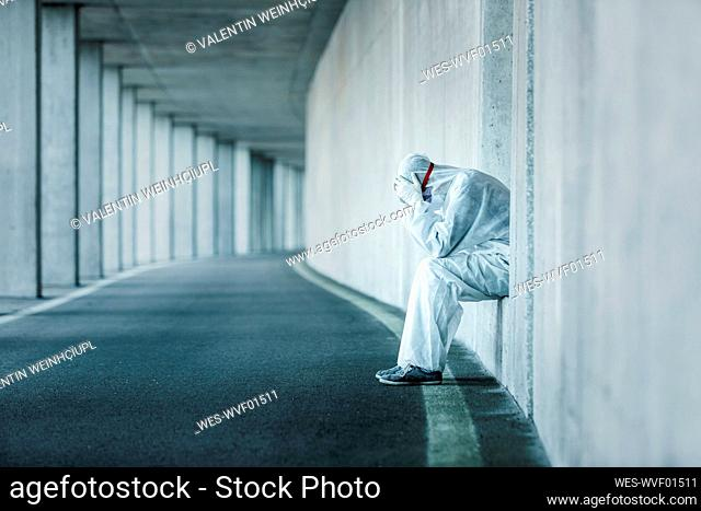 Despaired man wearing protective clothing sitting in a niche of a concrete wall in a tunnel