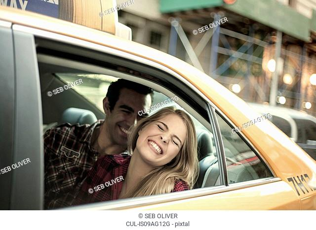 Young couple laughing in yellow cab, New York City, USA