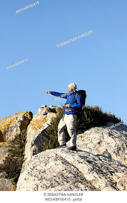 Spain, Andalusia, Tarifa, man on a hiking trip standing on rock pointing his finger