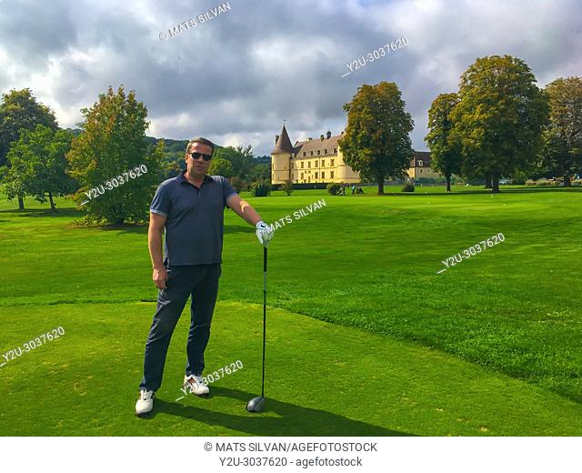 Proud Golfer Holding his Driver in a Sunny Day with a Castle in background in Chailly-Sur-Armancon in France