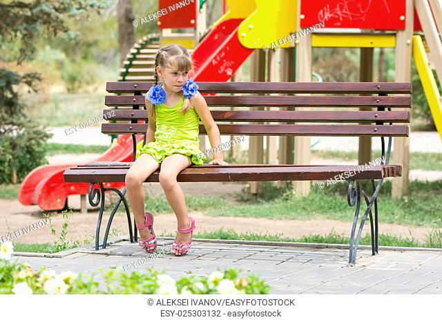 Upset girl bit her lip while sitting on the bench on the background of the playground