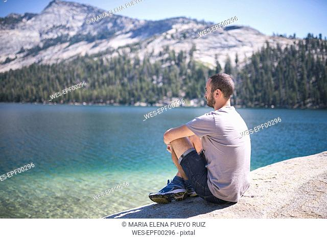 USA, California, Yosemite National Park, man sitting at mountain lake
