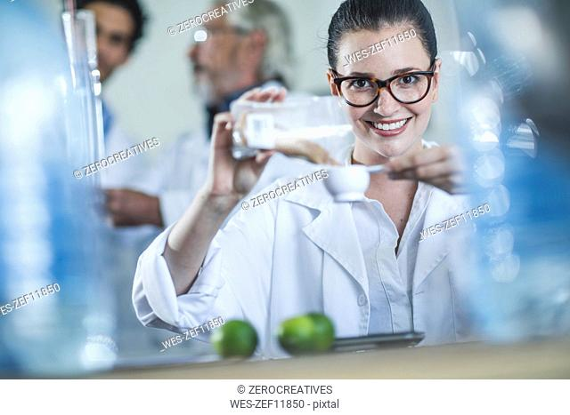 Distiller measuring coriander seeds for gin production