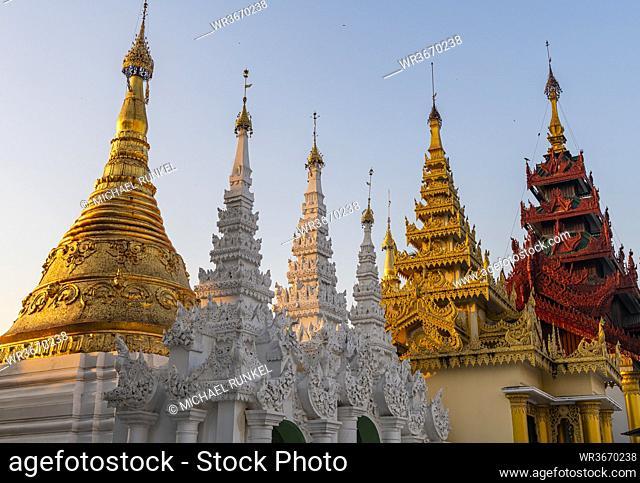 Myanmar, Yangon, Golden spires of Shwedagon pagoda at sunset