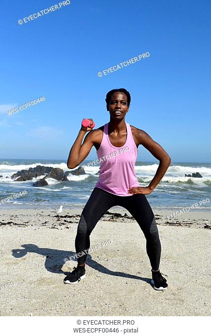 Woman doing fitness exercise with dumbbell on the beach