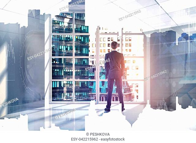 Back view of young businessman looking out of window in interior with city view and abstract business hologram. Futuristic innovation and finance concept