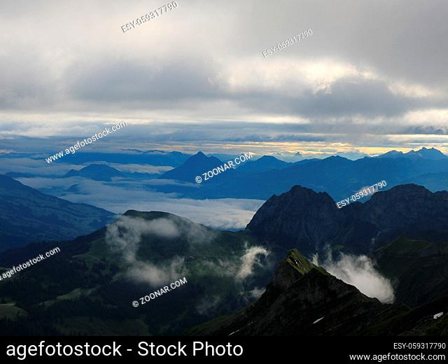Sunrise scene seen from Mount Brienzer Rothorn. View towards Stanserhorn and Lucerne. Fog lifting slowly after a rainy night