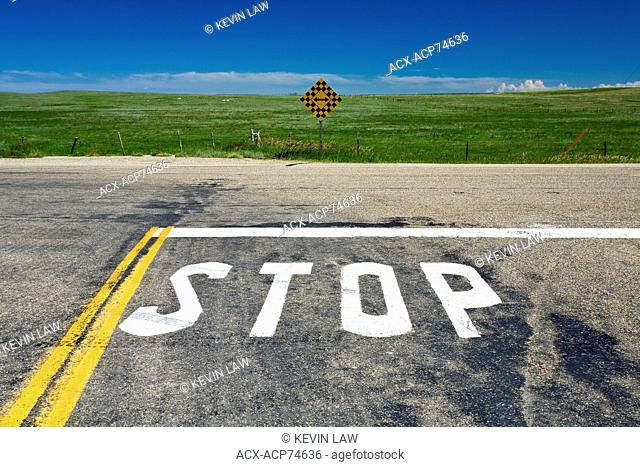 Stop sign painted on rural road with direction sign, south Alberta, Canada