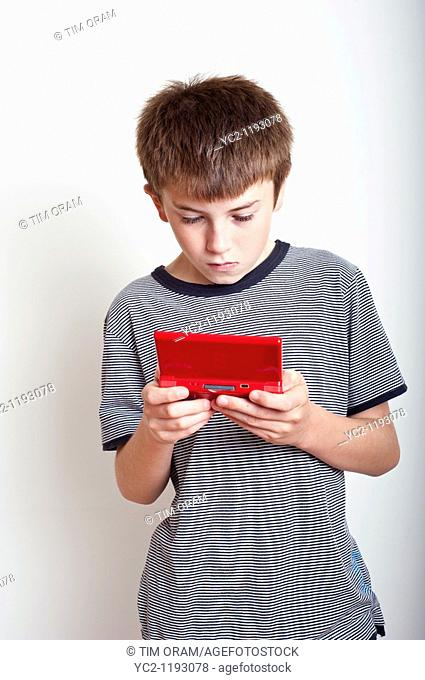 10 year old boy playing with a Nintendo DS handheld games console in the studio