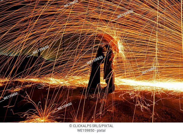 Couple under an umbrella to shelter from a shower of incandescent sparks created by the technique of steel wool, emilia romagna, italy
