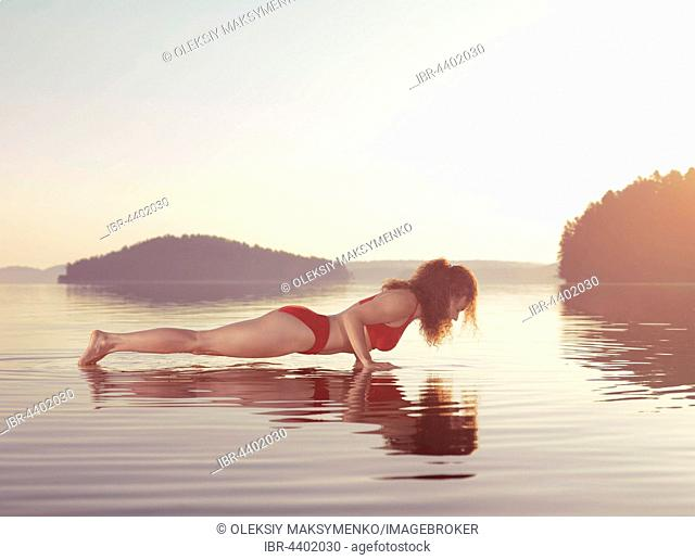 Young woman practicing Hatha yoga on a floating platform in water on the lake during misty morning light, Yoga or pilates Plank posture, Kumbhakasana