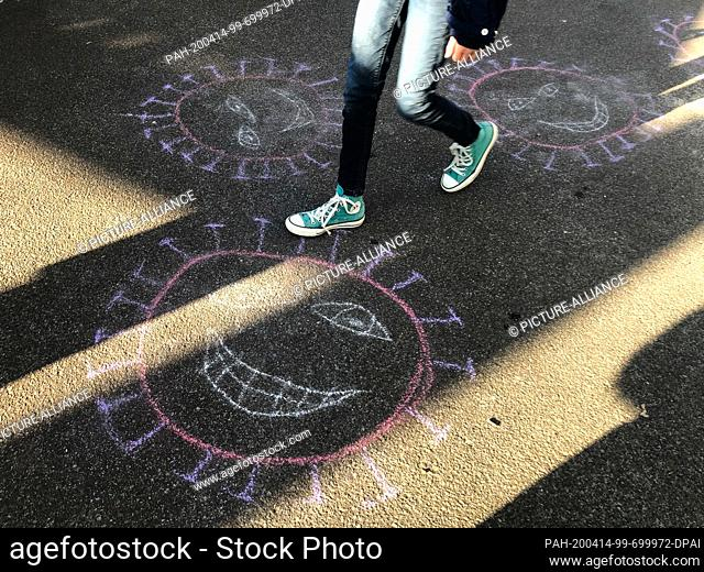 14 April 2020, Berlin: The depiction of the coronavirus has been painted with crayon by children on a street. Photo: Jörg Carstensen/dpa