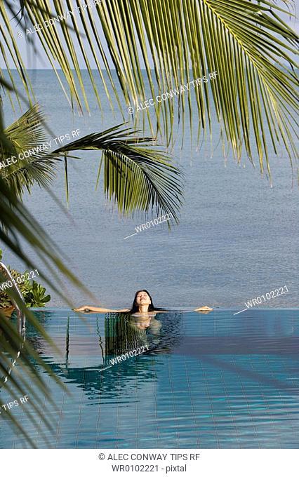 Thailand, Koh Samui. Thai Woman bathing in swimming pool next to sea