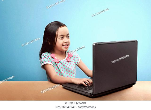 Smiling asian child with laptop computer on the table against blue background