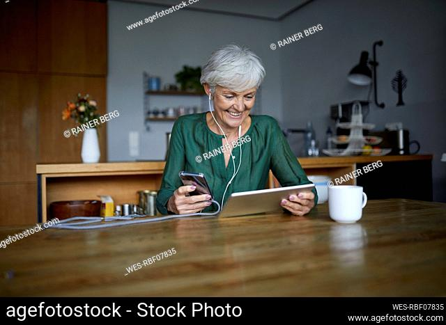 Senior woman listening to music while using smart phone and digital tablet at home