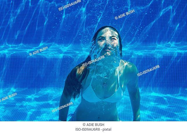 Underwater view of girl underwater swimming in swimming pool